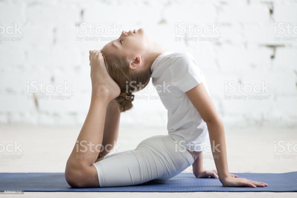 Girl child in raja bhudjangasana pose, white studio background stock photo