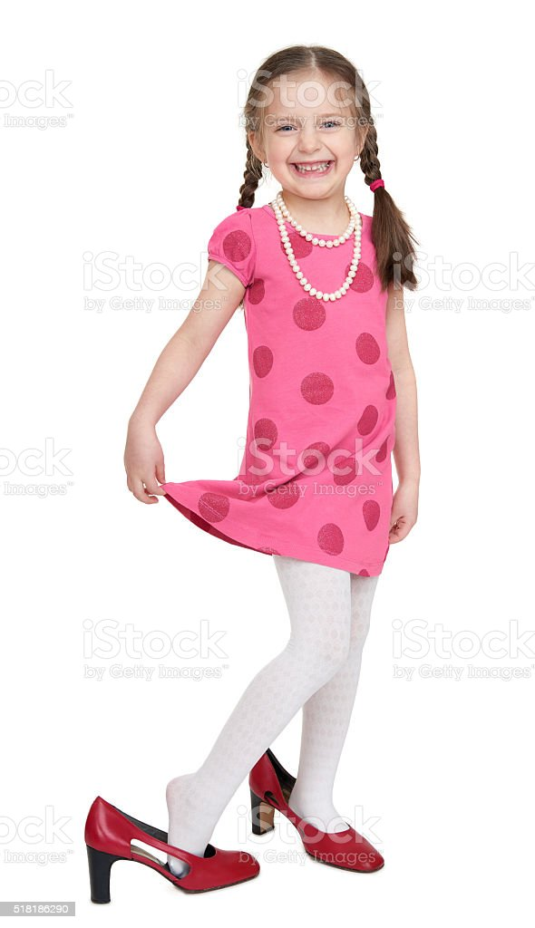 Girl child in red dress and shoes with high heels stock photo