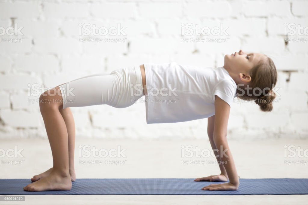 Girl child in Reverse Table Top pose, white studio background stock photo
