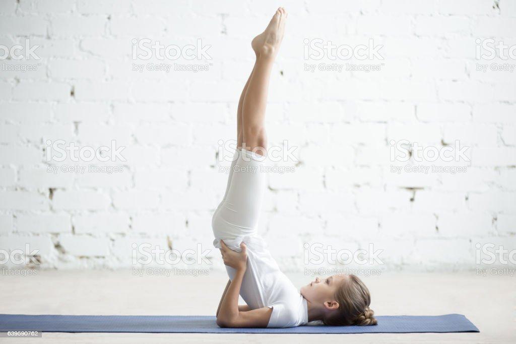 Girl child in Salamba Sarvangasana pose, white studio background stock photo