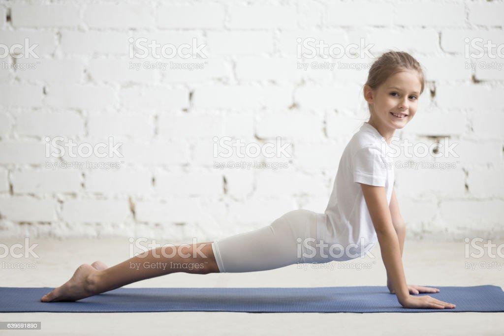 Girl child in upward facing dog pose, white studio background stock photo