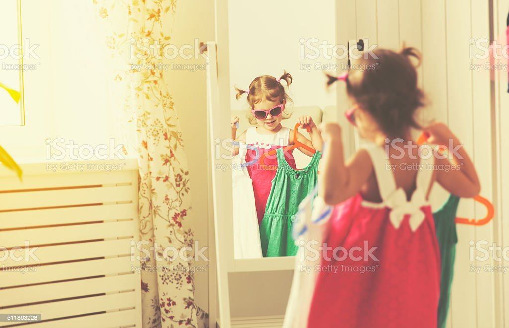 girl child looks into the mirror and choose dresses stock photo