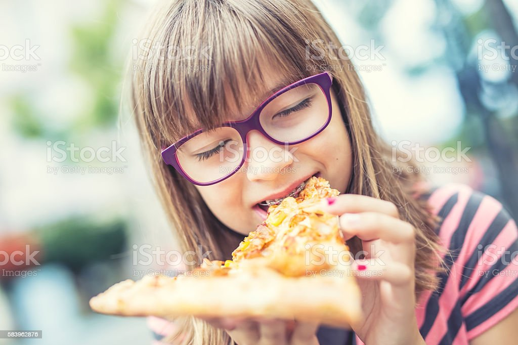 Girl child teenager with pizza. Child with braces and glasses. stock photo
