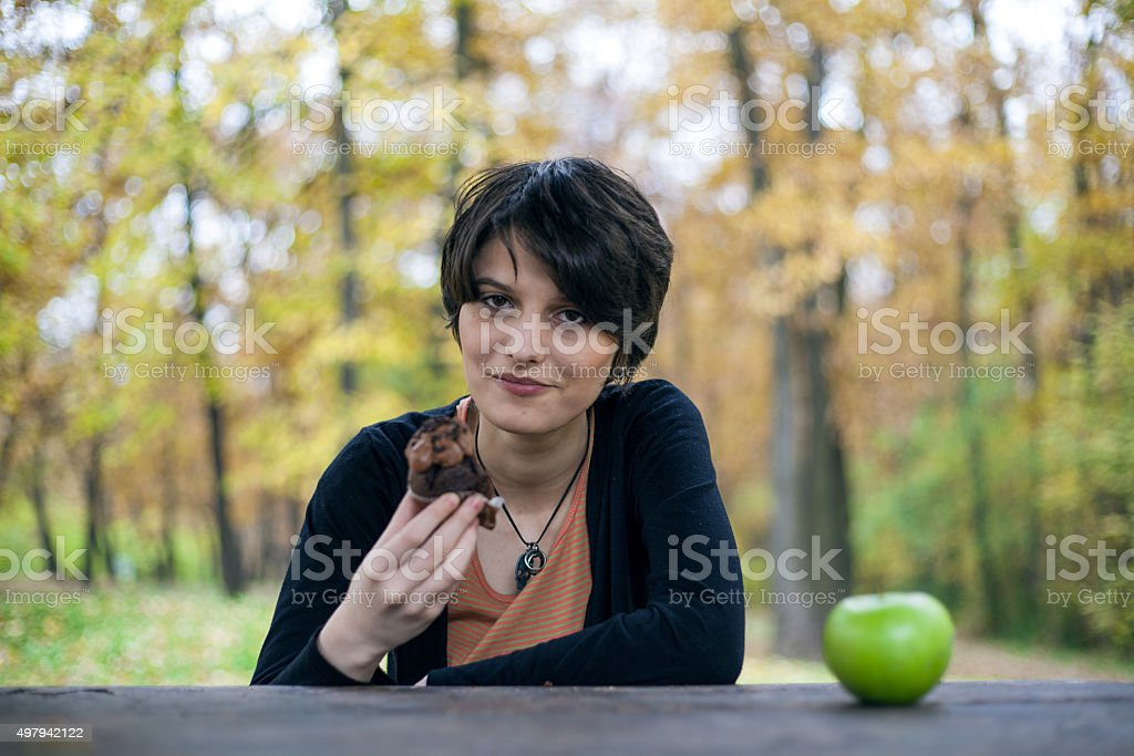 Girl chooses cupcake over apple royalty-free stock photo