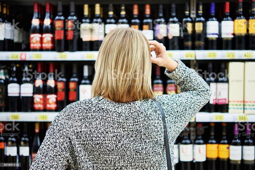 Girl chooses wine stock photo