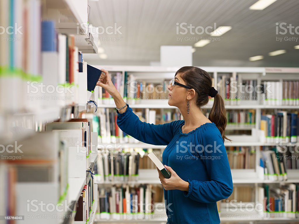 girl choosing book in library royalty-free stock photo