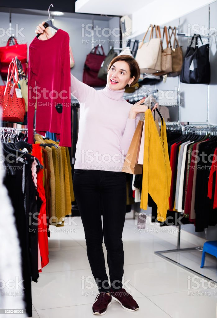 Girl choosing colorful blouse stock photo