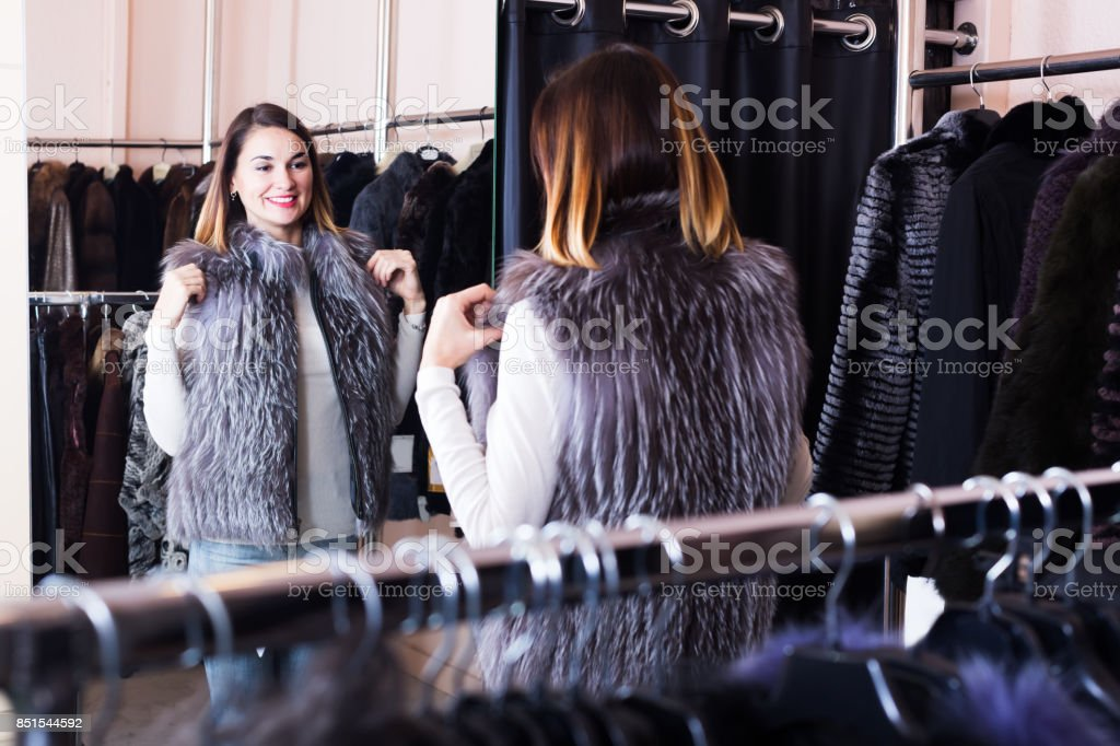 Girl choosing fur vest stock photo