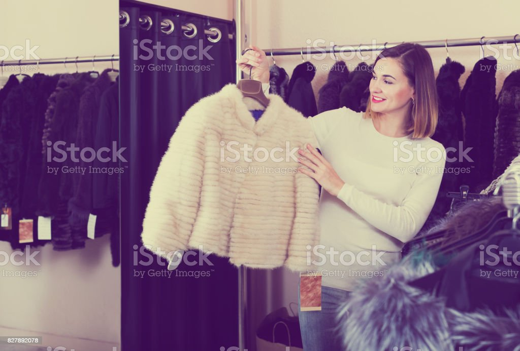 Girl choosing mink jacket stock photo