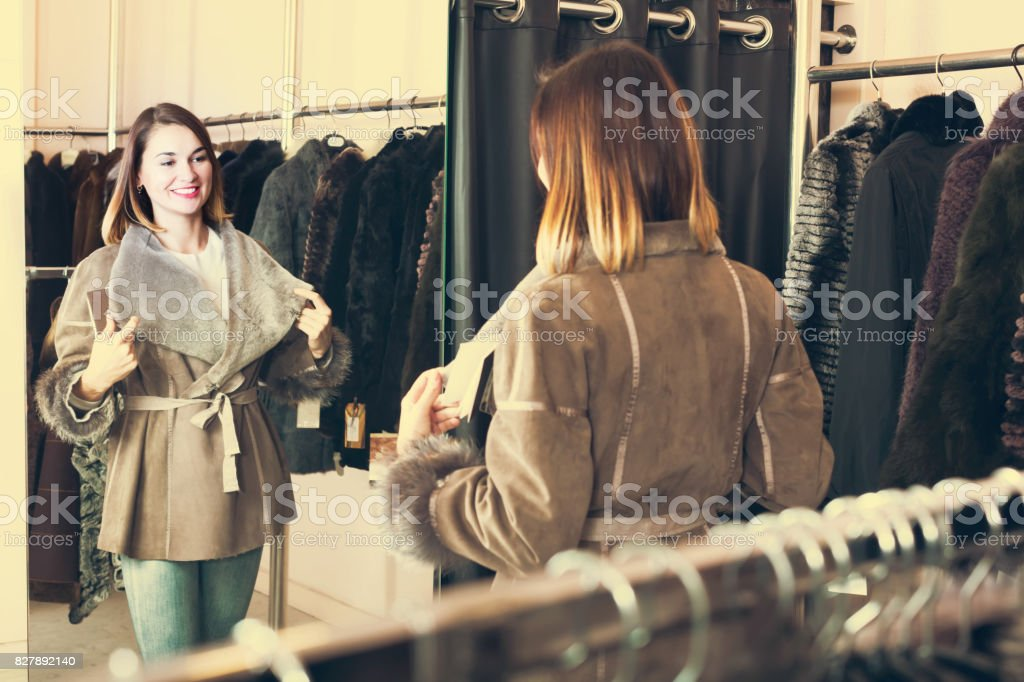 Girl choosing sheepskin coat stock photo