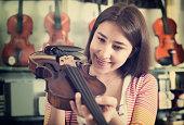 Girl choosing violin in music shop