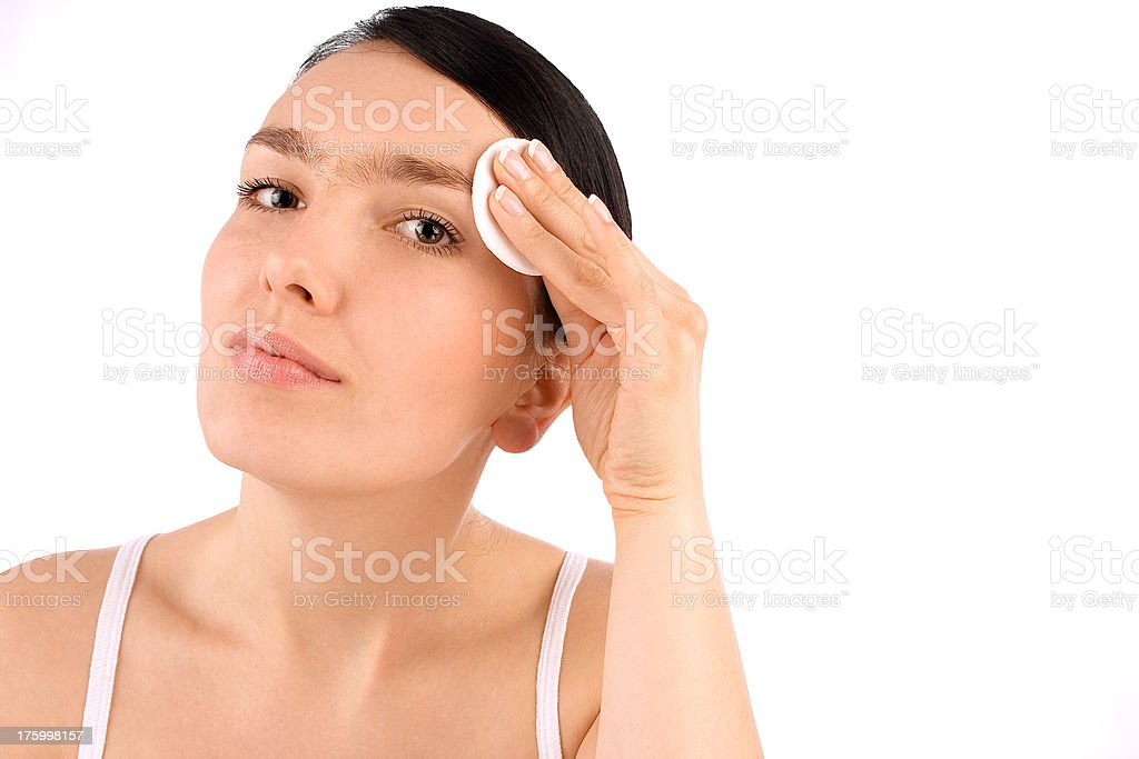 Girl cleaning her face with cotton pad stock photo