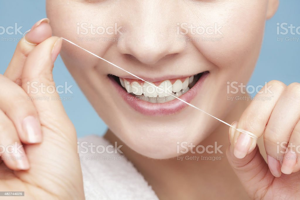 Girl cleaning teeth with dental floss. Health care stock photo