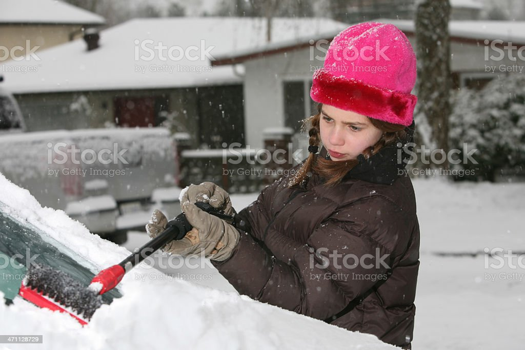 Girl clears Snow off Windshield royalty-free stock photo