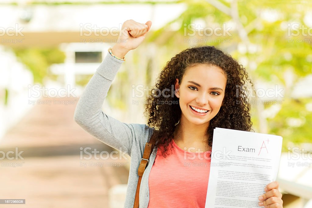 Girl Clenching Fist While Holding Result On College Sidewalk royalty-free stock photo