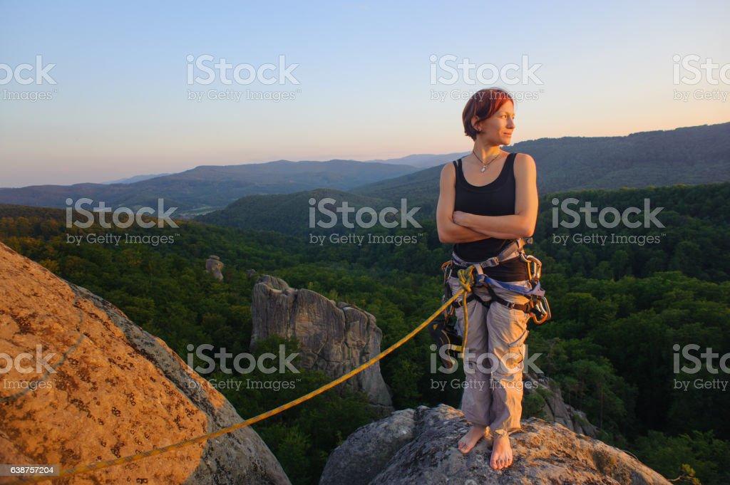 Girl climber on mountain peak on high altitude in evening stock photo