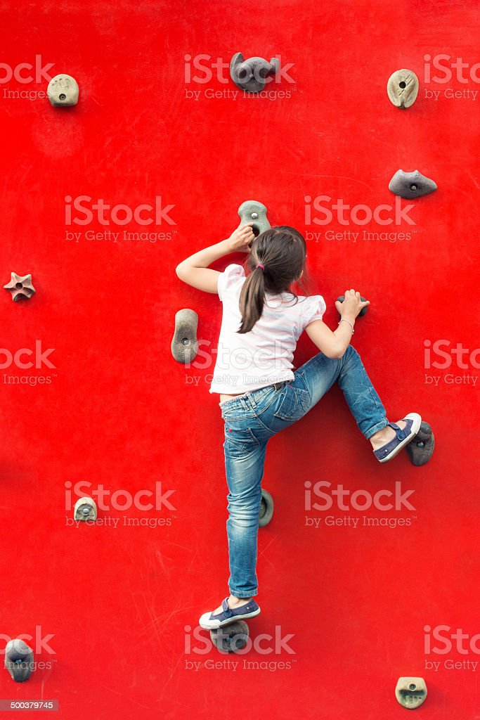 Girl climbing a red wall in a playground stock photo