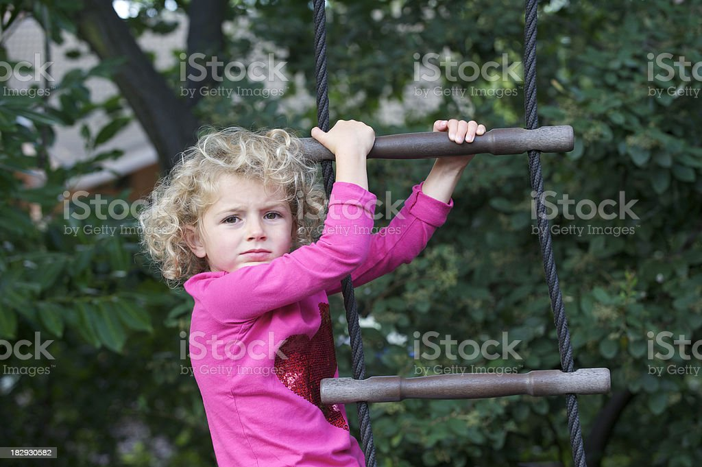Girl climbing a rope ladder stock photo