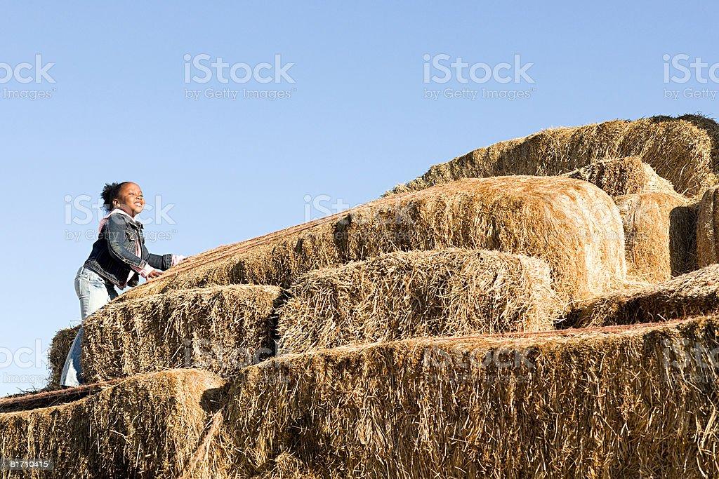 A girl climbing bales of hay royalty-free stock photo