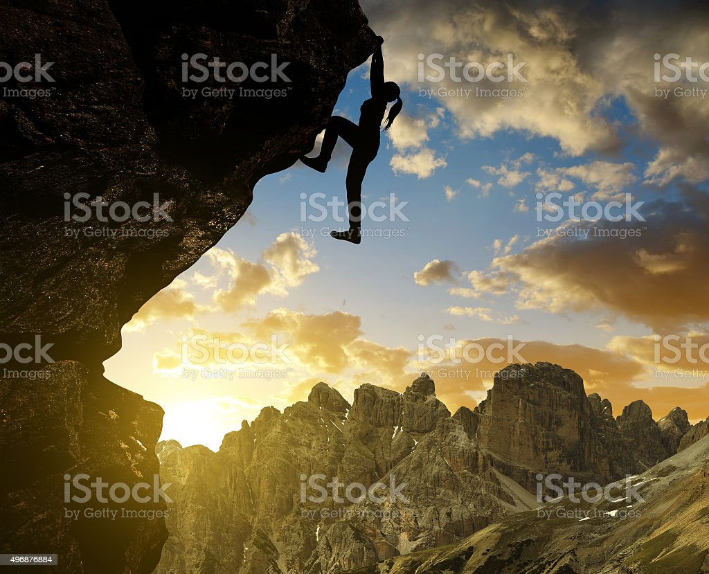 girl climbing on rock at sunset in Sexten Dolomites stock photo