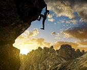 girl climbing on rock at sunset in Sexten Dolomites