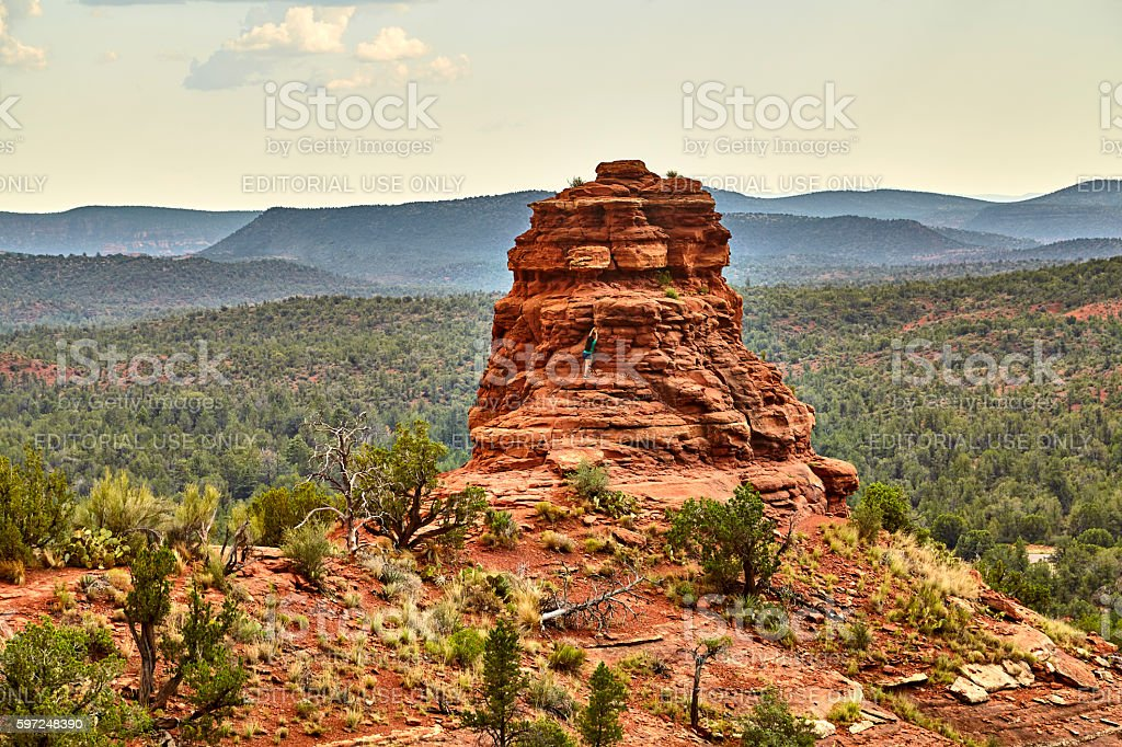 Girl climbing Red Rock Face at a Scenic Overlook stock photo