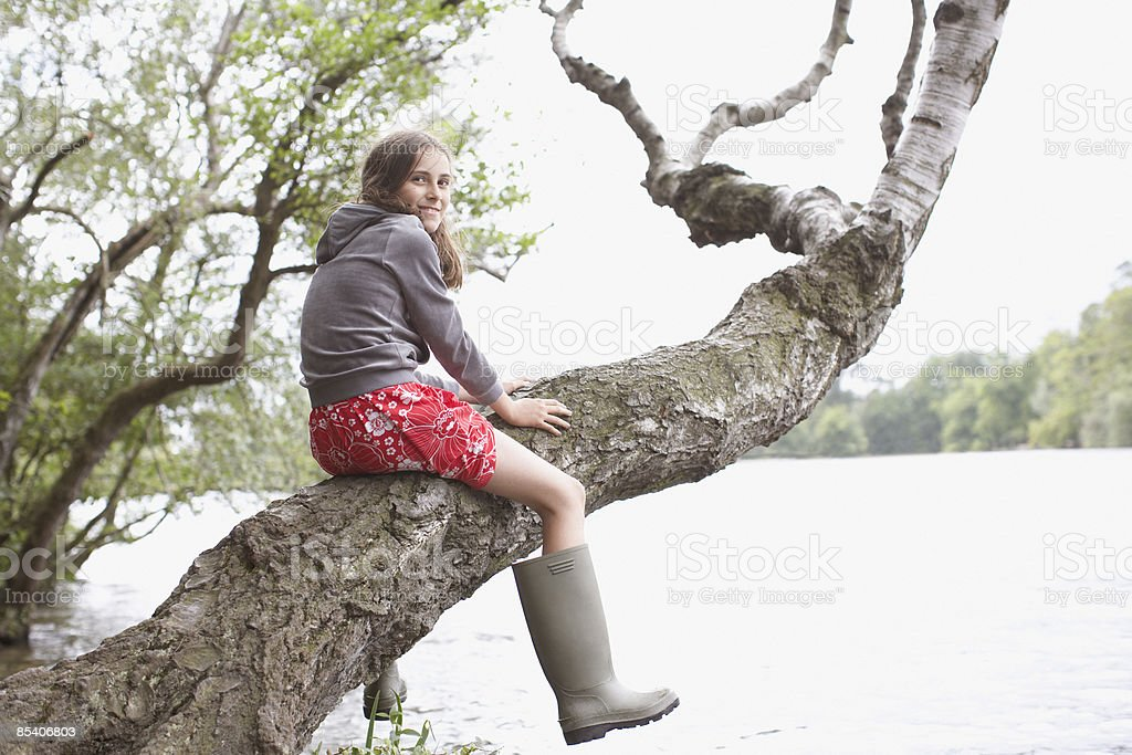 Girl climbing tree near lake royalty-free stock photo