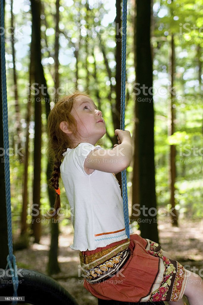 girl, climbing up a rope in the woods royalty-free stock photo