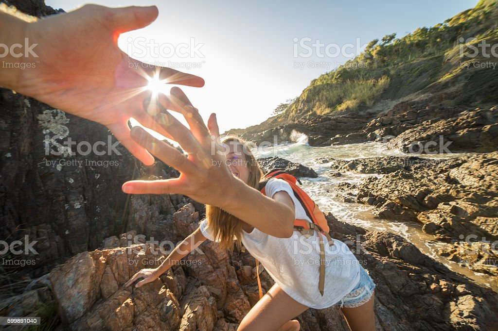 Girl climbs on cliff, partner pulls out hand for assistance stock photo