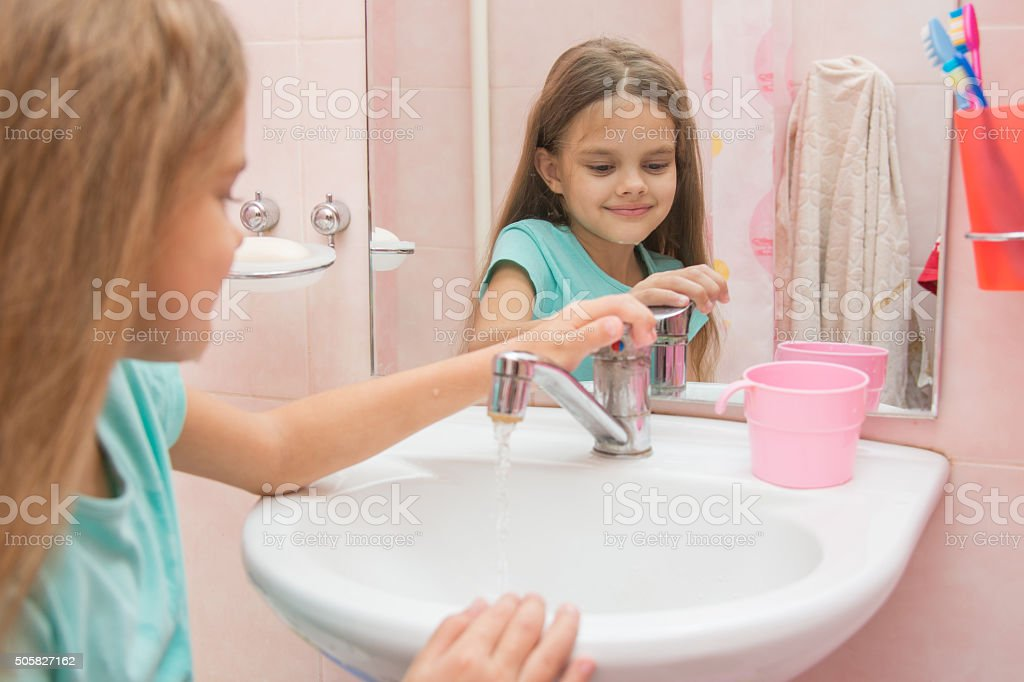 Girl closes after washing the mixer tap in the bathroom stock photo
