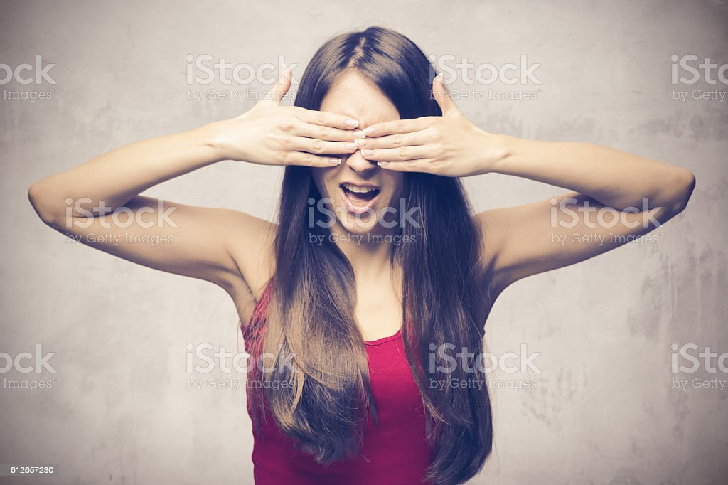 Girl closes eyes with her hands stock photo