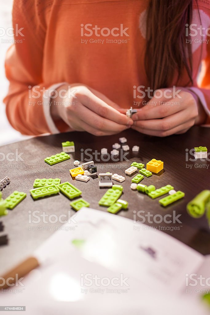 Girl collects toy of the blocks stock photo