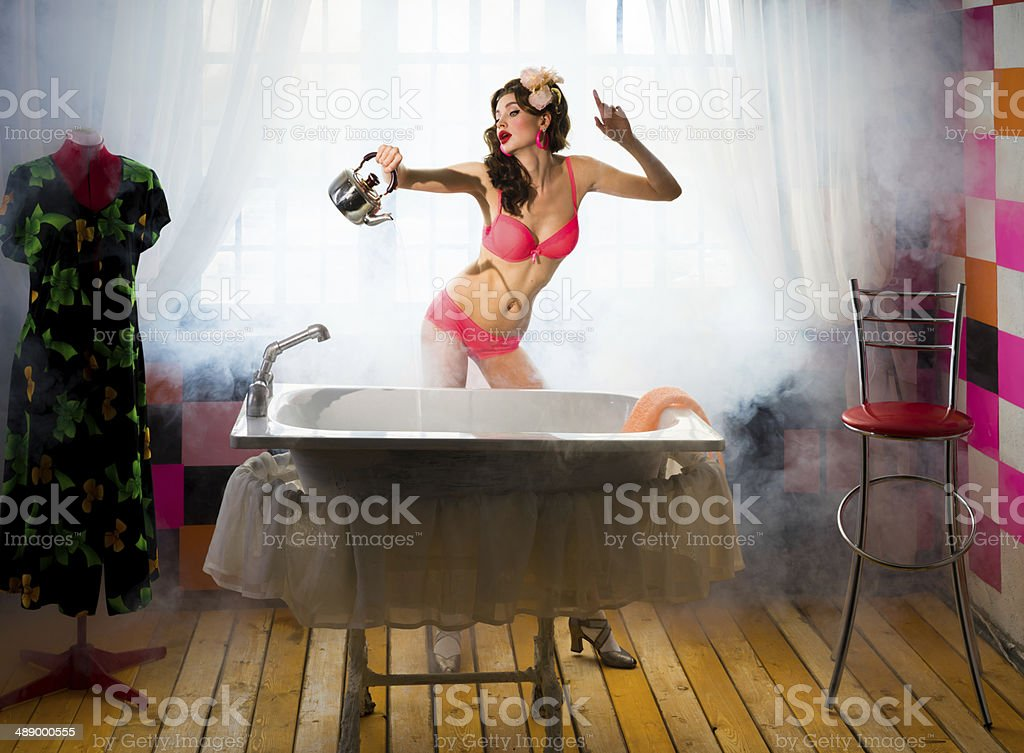 Girl collects water in the bath stock photo