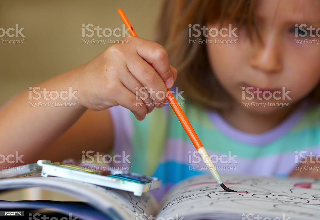 Girl coloring a book royalty-free stock photo
