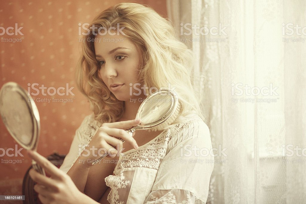 girl combing her hair by the window royalty-free stock photo