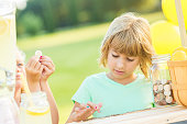 Girl concentrates while counting lemonade stand profits