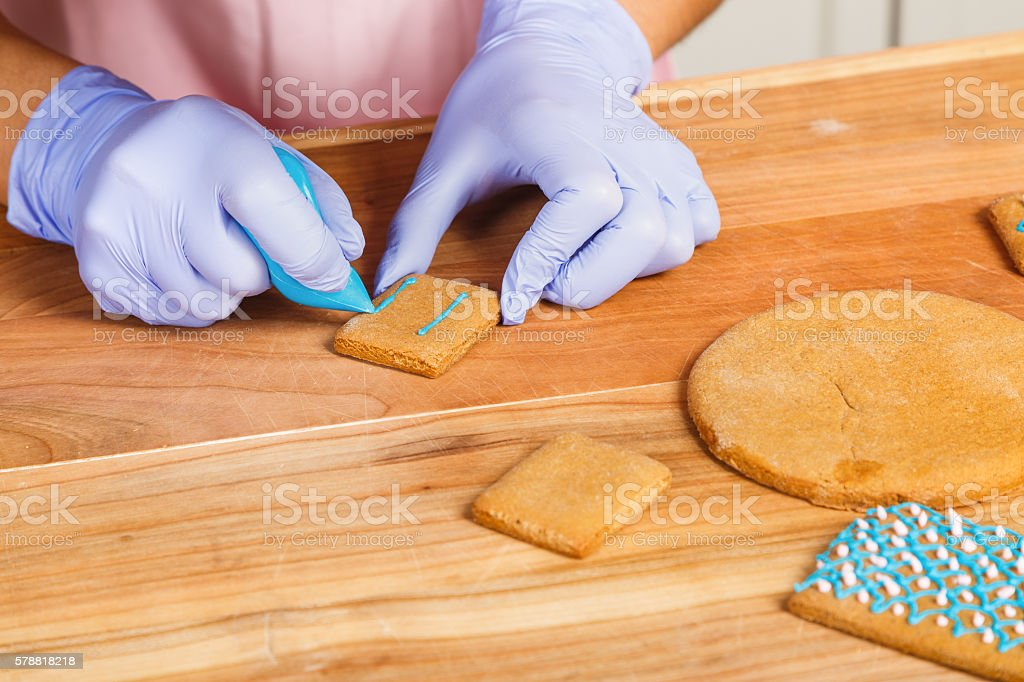 Girl confectioner, decorating gingerbread with bag with blue cream stock photo