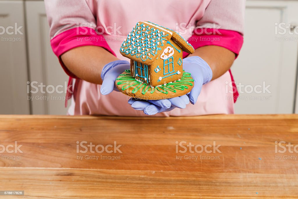 Girl confectioner holding gingerbread house in her hands stock photo