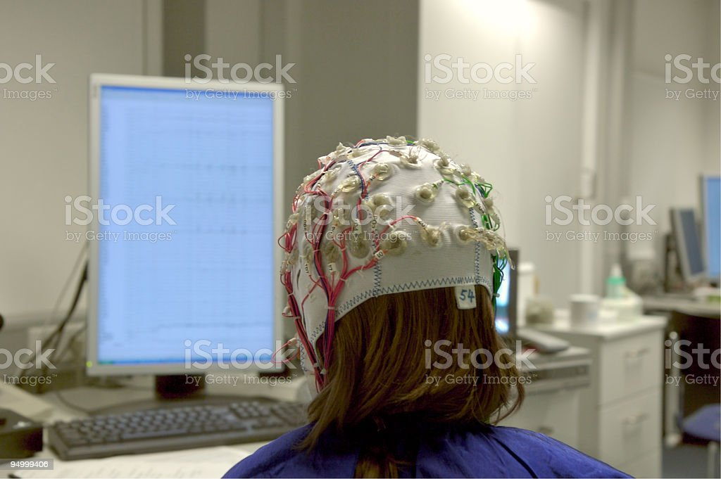 girl connected with cables for EEG in front of screen stock photo