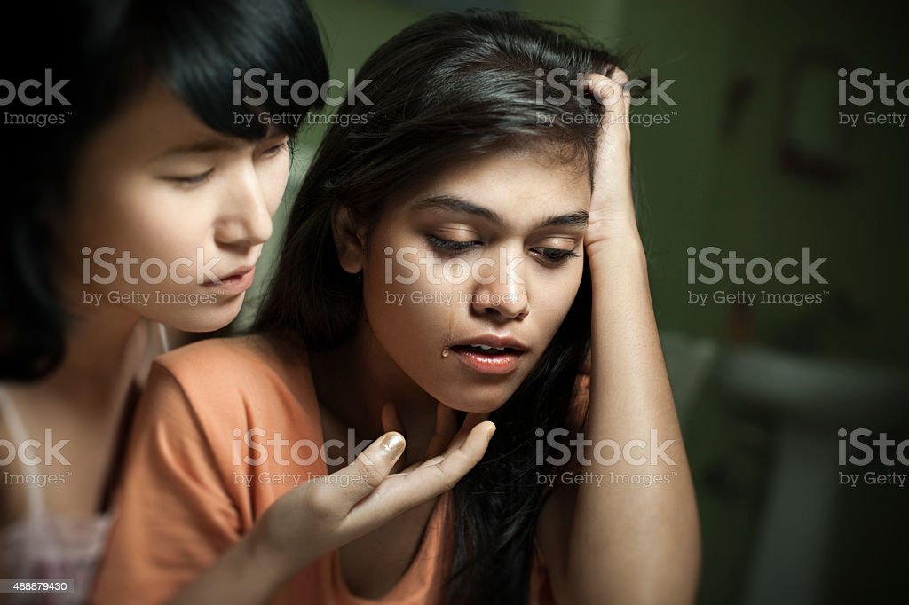 Girl consoling to her sad, crying roommate of different ethnicity. stock photo
