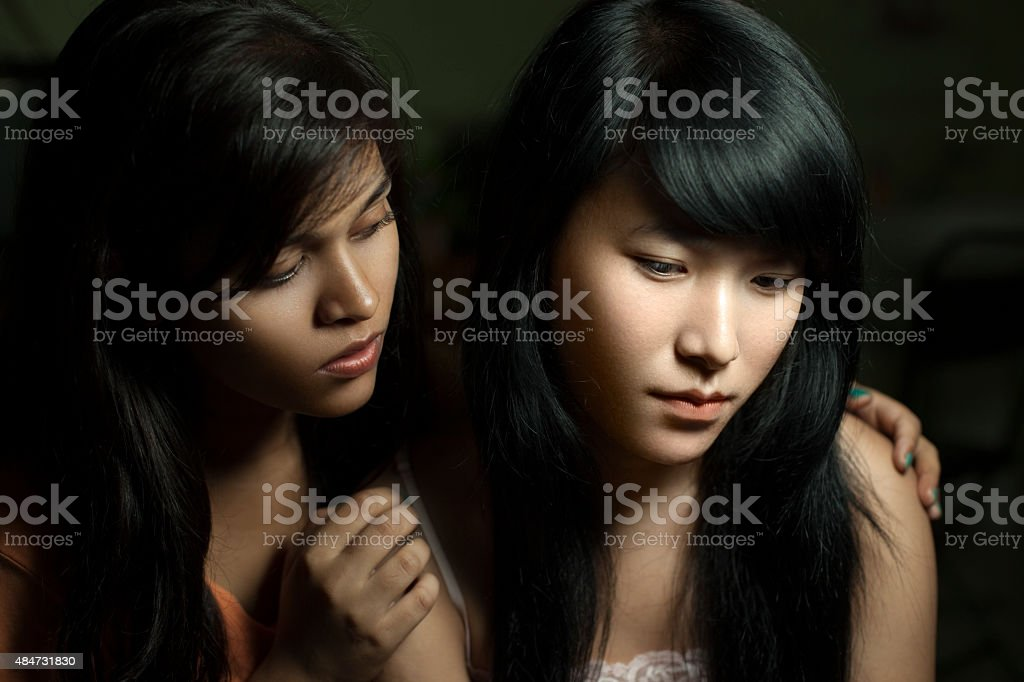Girl consoling to her sad female roommate of different ethnicity. stock photo