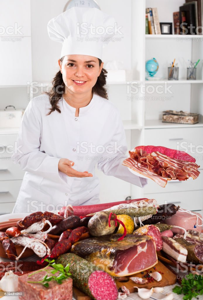 Girl cook costs which sausages and smoked meat stock photo