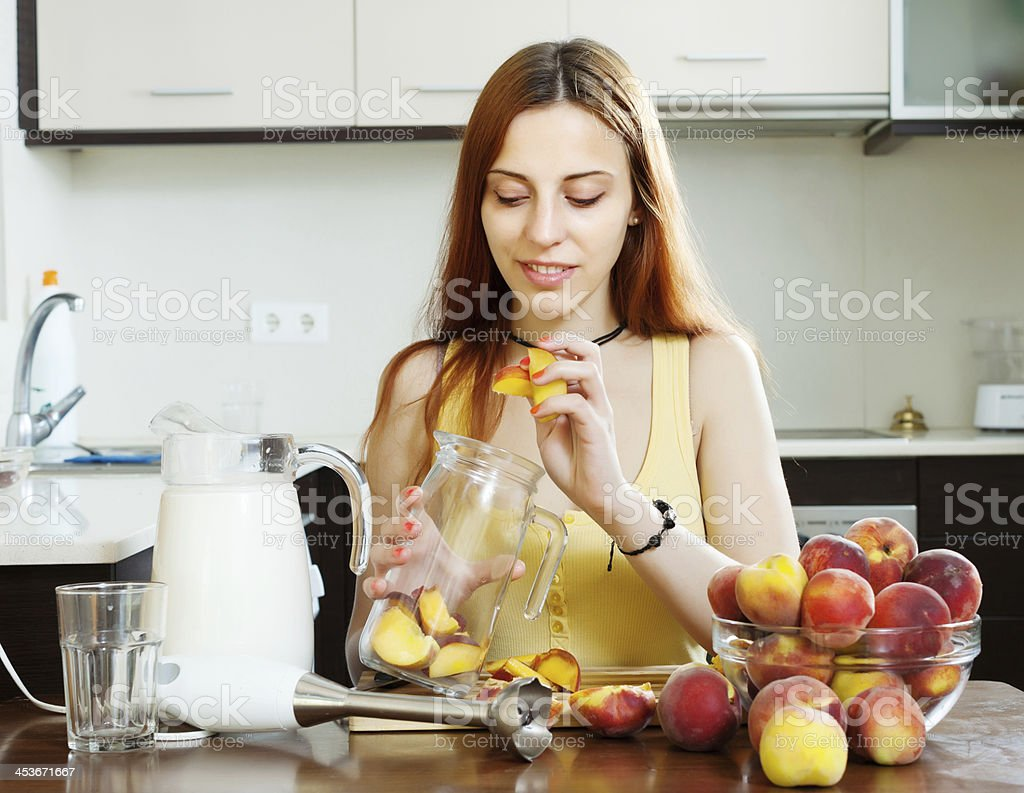 girl cooking  beverages   from peaches at  kitchen royalty-free stock photo