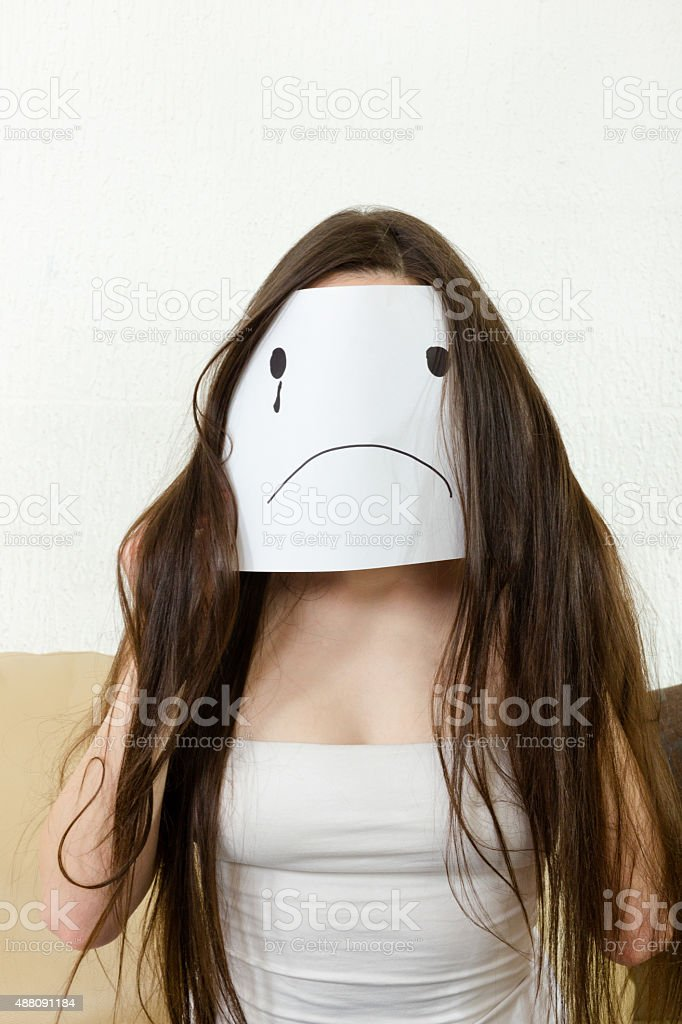 girl cover face with smile drawn on paper with tear stock photo