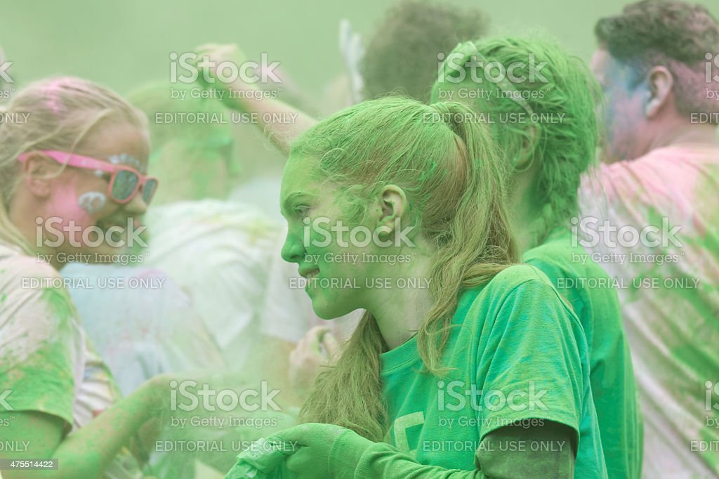 Girl covered with green color powder stock photo