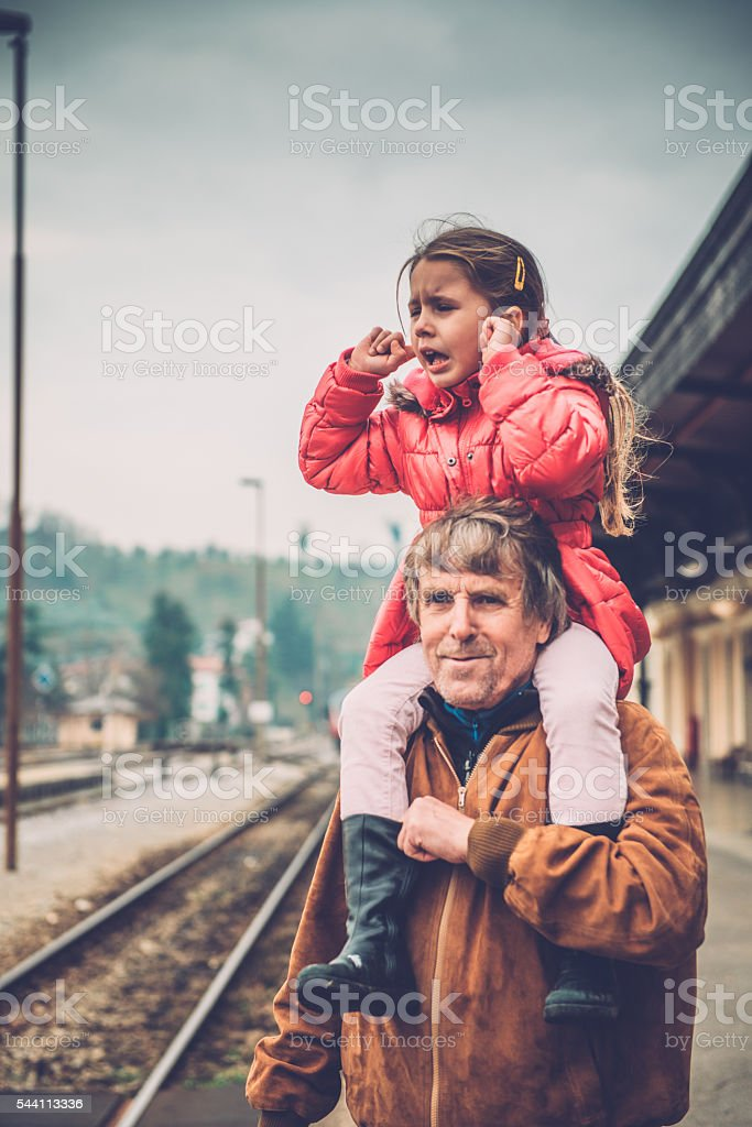 Girl Covering Ears while Riding on Grandfather's Shoulder, Railway Station stock photo
