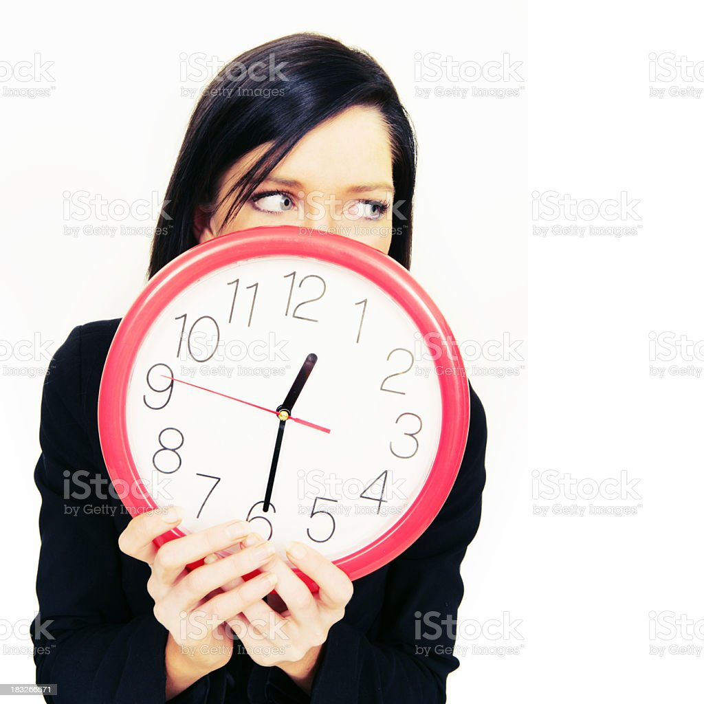 Girl covering mouth with a clock looking at side stock photo