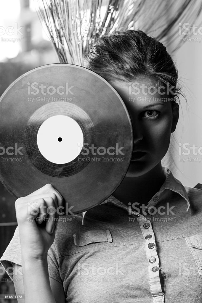 Girl covers her face with a vinyl disc. royalty-free stock photo