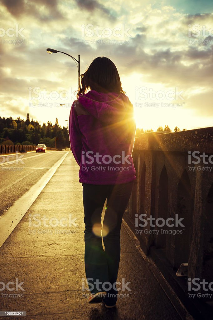 Girl crossing a bridge stock photo