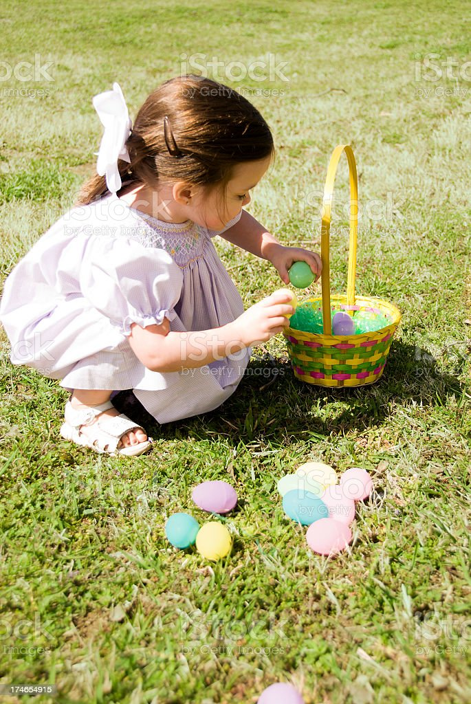 Girl crouched on grass taking Easter eggs from basket royalty-free stock photo